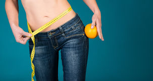 Healthy female body with orange and measuring tape. Healthy fitness and eating lifestyle concept. Royalty Free Stock Photography