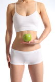 Healthy female torso white underwear holding apple. Beautiful, fit healthy female torso, wearing white underwear. Model holding green apple in front of stomach Royalty Free Stock Photography