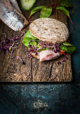 Healthy fish sandwich with grain bread and fish on rustic cutting board Royalty Free Stock Photography