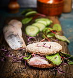 Healthy fish sandwich with herring, cucumber and sprouts on rustic kitchen table. Side view royalty free stock images