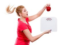 Woman holding apple and weight machine Stock Image