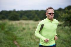 Healthy fit man wearing sunglasses jogging through rural grassland Royalty Free Stock Image