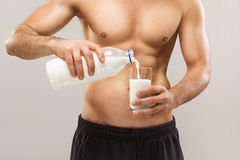 Healthy fit muscular shirtless man pouring milk Royalty Free Stock Photos