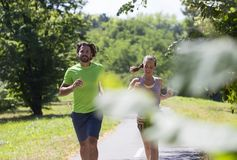 Healthy, fit and  sportive couple running in park Stock Photo