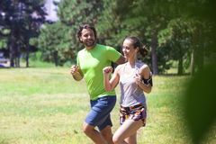 Healthy, fit and sportive couple running in park. At summer morning Royalty Free Stock Photos