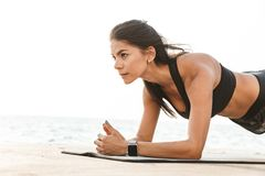 Healthy fit sportswoman doing exercises. Healthy fit sportswoman doing yoga exercises on a fitness mat outdoors, plank exercise royalty free stock image