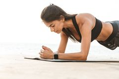 Healthy fit sportswoman doing exercises. Healthy fit sportswoman doing yoga exercises on a fitness mat outdoors, plank exercise royalty free stock photography