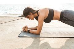 Healthy fit sportswoman doing exercises. Healthy fit sportswoman doing yoga exercises on a fitness mat outdoors, plank exercise stock image