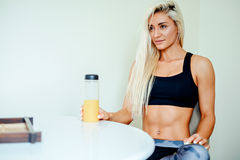 Healthy Fit woman in sportswear sitting on chair drinking juice Royalty Free Stock Images