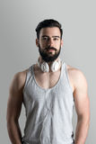 Healthy fit young bearded man in singlet with headphones around neck Royalty Free Stock Photography