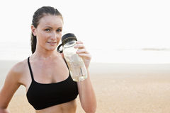 Healthy fit young woman on beach drinking water. Front view of healthy fit young woman on beach drinking water Royalty Free Stock Image