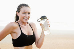 Healthy fit young woman on beach drinking water. Happy healthy fit young woman on beach drinking water Royalty Free Stock Photos