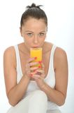 Healthy Fit Young Woman Drinking a Glass of Fresh Orange Juice. A DSLR royalty free image, of attractive young healthy woman, with dark pulled back hair off her Stock Photography