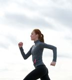 Healthy fit young woman running outdoors Stock Photography