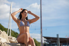 Healthy fit young woman on stone pier Royalty Free Stock Photography
