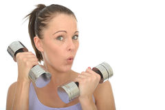 Healthy Fit Young Woman Training With Dumb Bell Weights Pulling Silly Facial Expression. A DSLR royalty free image, a healthy fit young woman, holding two or 2 Royalty Free Stock Image