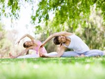 Young women exercising in the park. Healthy and fit young women doing yoga in the park Royalty Free Stock Photography