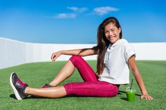 Healthy fitness Asian girl drinking green smoothie. Cute happy smiling woman relaxing during cardio training workout on outdoor grass gym enjoying vegetable stock photos