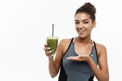 Healthy and Fitness concept - Beautiful American African lady in fitness clothing drinking healthy vegetable drink Royalty Free Stock Photos