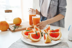Healthy fitness diet breakfast. Detox refreshing smoothie. Focus on sliced grapefruit. Girl background. Copy space Royalty Free Stock Images