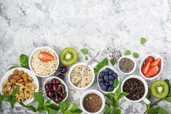 Healthy fitness food from fresh fruits, berries, greens, super food: kinoa, chia seeds, flax seed, strawberry, blueberry. Kiwi, cherry, almonds, walnuts, mint Royalty Free Stock Image