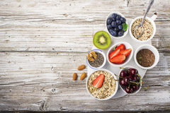 Healthy fitness food from fresh fruits, berries, greens, super food: kinoa, chia seeds, flax seed, strawberry, blueberry. Kiwi, cherry, almonds, walnuts, mint Royalty Free Stock Photos