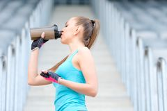 Healthy fitness girl drinking protein shake. Woman drinking sports nutrition beverage while working out. Portrait of healthy fitness girl drinking protein shake royalty free stock photo
