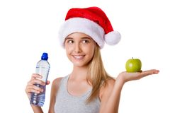 Healthy fitness girl in Santa hat holding apple and bottle of wa Royalty Free Stock Photo