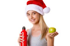 Healthy fitness girl in Santa hat holding apple and red bottle,isolated Royalty Free Stock Photography