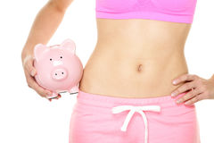 Healthy fitness lifestyle is expensive. Fit woman holding piggy bank - healthy and fitness costs money concept. Close up of female stomach isolated on white royalty free stock photo