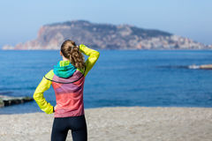 Healthy and fitness lifestyle Young woman standing on beach in g Stock Image