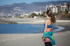 Healthy and fitness lifestyle Young woman standing on beach. Young woman standing in gym clothing with blurred sea and mountains on background Royalty Free Stock Image