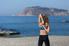 Healthy and fitness lifestyle Young woman stretching on beach in Stock Image