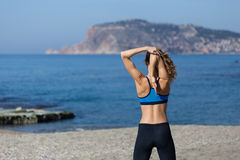 Healthy and fitness lifestyle Young woman stretching on beach in Stock Images