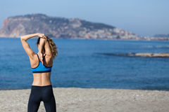Healthy and fitness lifestyle Young woman stretching on beach in Stock Photography
