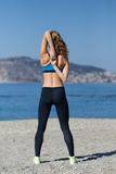 Healthy and fitness lifestyle Young woman stretching on beach Stock Photo