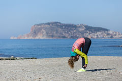 Healthy and fitness lifestyle Young woman stretching on beach. Healthy and fitness lifestyle Young woman stretching and exercising by seaside with sea and Alanya Royalty Free Stock Image