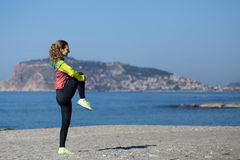 Healthy and fitness lifestyle Young woman stretching on beach Royalty Free Stock Image