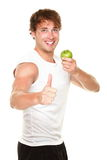 Healthy fitness man. Eating apple showing thumbs up success sign for weight loss. Young muscular sporty fit man isolated on white background Royalty Free Stock Image
