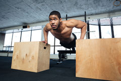Healthy fitness man doing push-ups in the gym Stock Image
