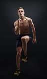 Healthy and fitness man running on black background. Stock Photo