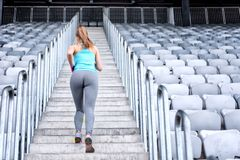 Healthy fitness woman jogging and running outdoors in city stadium, working out Stock Photos