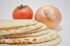 Healthy Flat Bread. A stack of flat bread with an onion and a tomato in the background stock image