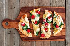 Healthy flatbread pizza on wooden paddle board. Healthy flat bread pizza with melted mozzarella, tomatoes, spinach and artichokes, above view on wooden paddle Stock Images