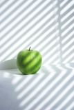 Healthy food. Green apple in white striped background Stock Photography