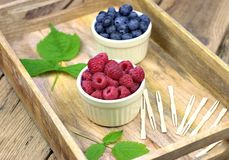 Fresh ripe blueberries and raspberries in two bowls. Healthy food,agriculture,harvest and fruit concept: fresh ripe blueberries and raspberries in two bowls on Stock Photo