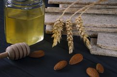 Healthy food. Air dietetic loaves lie on a dark wooden table on a dark background next to the ears of wheat and honey royalty free stock image