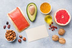 Healthy food antioxidant products: fish and avocado, nuts and fish oil, grapefruit on grey concrete background.  stock photography