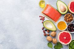 Healthy food antioxidant products: fish and avocado, nuts and fish oil, grapefruit spinach and oil on a gray concrete background. Copy space royalty free stock image