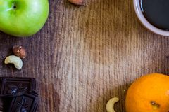 Healthy food. apple, orange, nuts, dark chocolate and black coffe. On a wooden cutboard. Flat top view stock photos